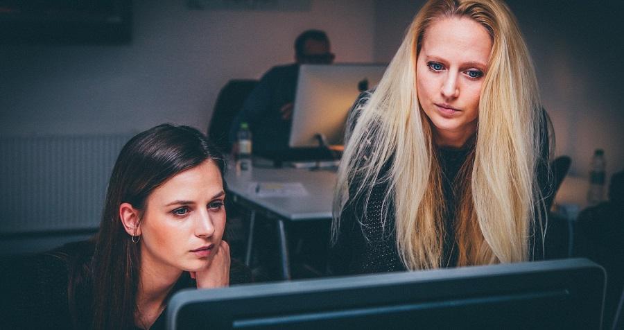 Twee vrouwen achter een computerscherm die nadenken