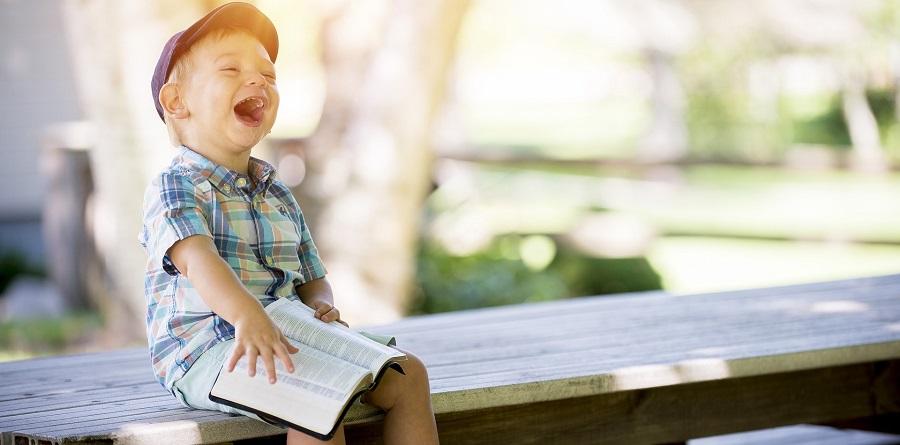 Jongetje dat smakelijk lacht om de taalfoutjes van een ander op Social Media. Maar laaggeletterdheid is een groot probleem.